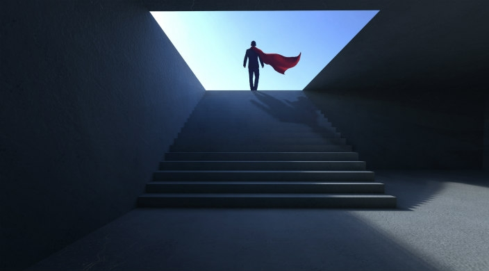 Shadowy profile of a man in a superhero cape walking up a flight up stairs
