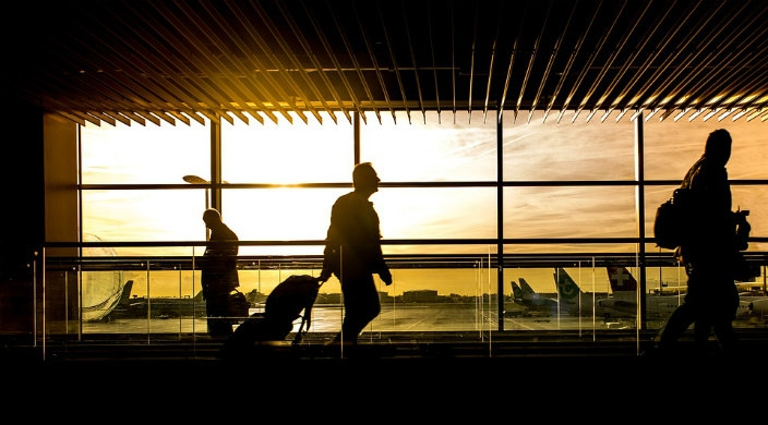 Silhouette of people carrying luggage through an airport with p;lanes out the window behind them