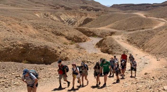 Teens climbing a desert mountain