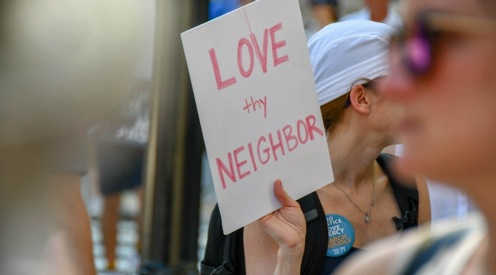 Protester holding a sign that says: Love thy Neighbor