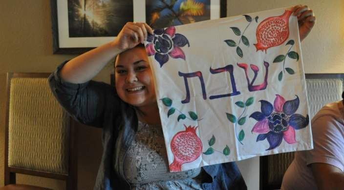 Amanda Ryan smiles while holding up a challah cover with Hebrew words and a hand drawn pomegranate