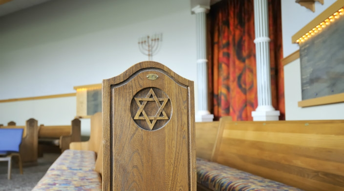 View of a synagogue sanctuary with the focal point being a wooden pew with a Star of David carved on its side