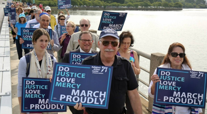 People marching over a bridge holding signs that read DO JUSTICE LOVE MERCY MARCH PROUDLY