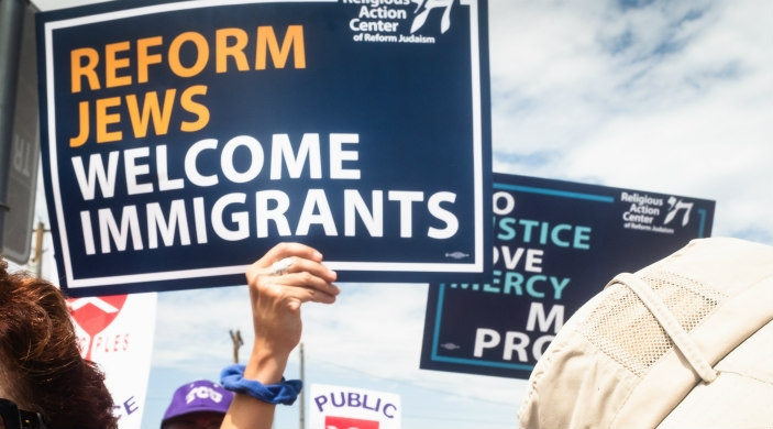 Person holding a sign that reads REFORM JEWS WELCOME IMMIGRANTS