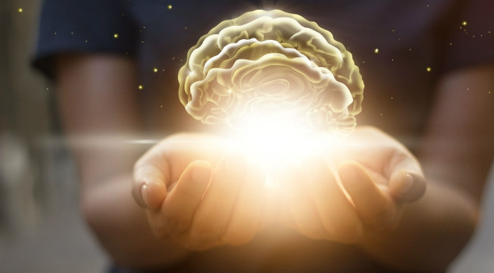 Background figure gently holding an image of the brain on a bed of light in open palms of the hand
