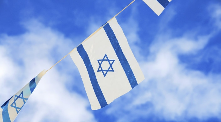 Israeli flags flying on a string; blue sky and clouds in the background