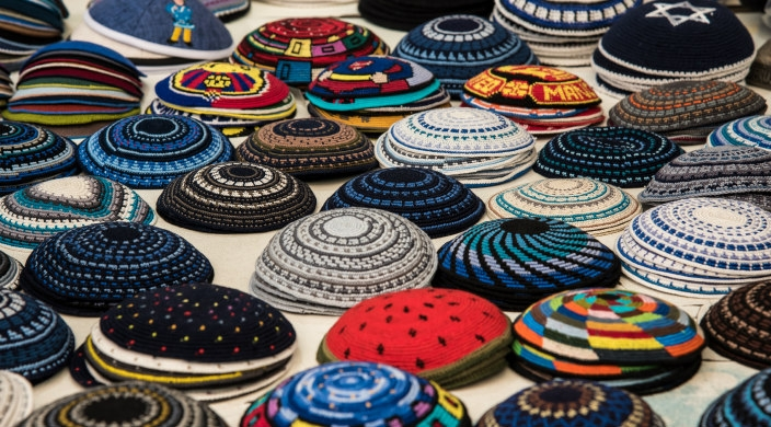 Assortment of knit kippot in piles on a table