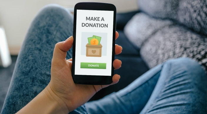 Hand holding a smartphone with a large DONATE button