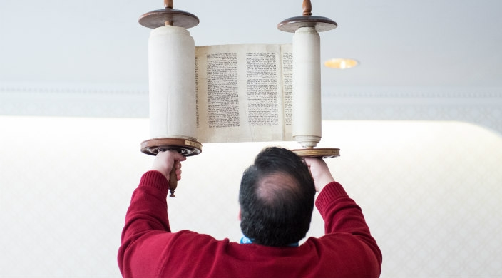 Man in a red sweater facing away from the camera while holding the Torah above his head