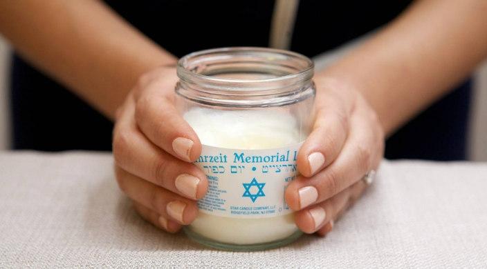 Womans hands holding a Yahrzeit candle