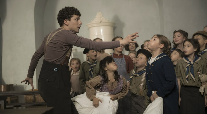 Still image from the film Resistance showing Jesse Eisenberg as Marcel Marceau engaging with a group of children