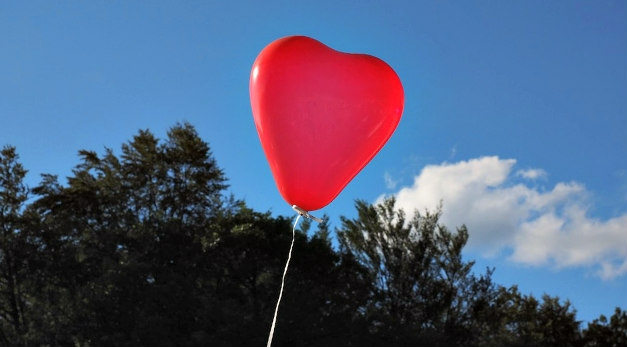 Red heart balloon rising into a blue sky over treetops