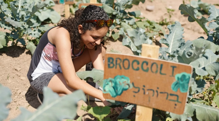 Smiling teen girl digging in the dirt next to a hand painted sign that says BROCCOLI in both Hebrew and English