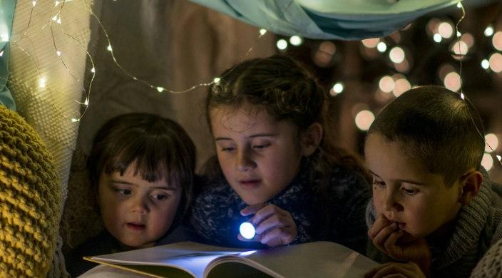 Three children using a flashlight to read a book inside a dark pillow fort