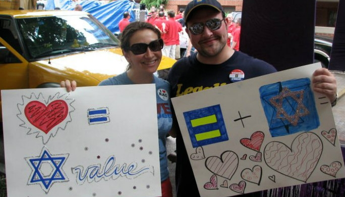Two smiling people holding Jewishly themed Pride Parade signs
