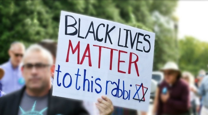 Blurred image with a sharp focus on a protest sign that reads BLACK LIVES MATTER TO THIS RABBI