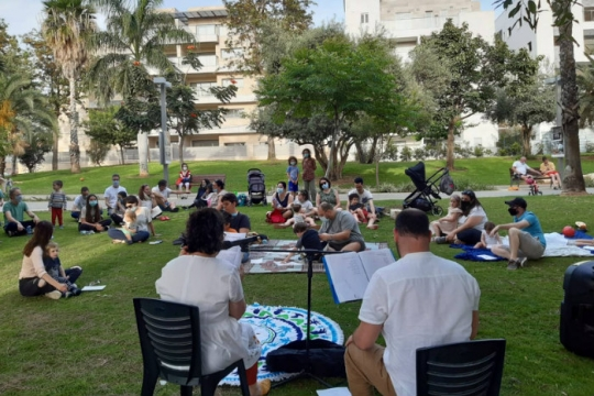 Synagogue memeber sit on the grass in a park and wear face masks during an outdoor Shabbat servicerk