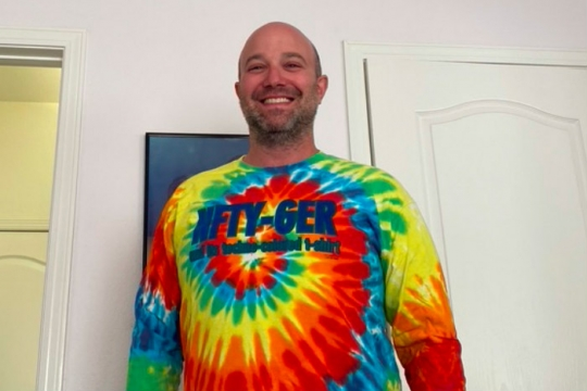 The author smiles while wearing a long sleeved tie dyed shirt that says NFTY GER across the front