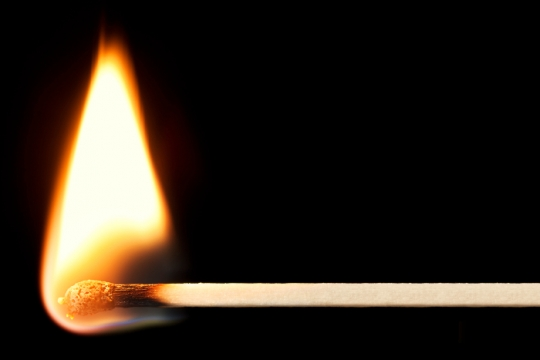 Closeup of a burning match against a black background