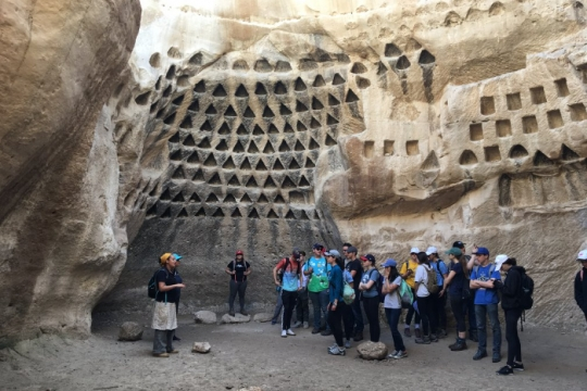 Group of students standing in an ancient cave with a teacher at the front