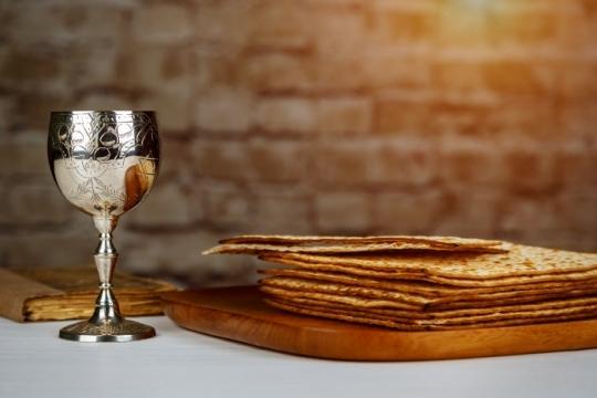 Pile of matzah atop a wooden platter next to a silver Kiddush cup