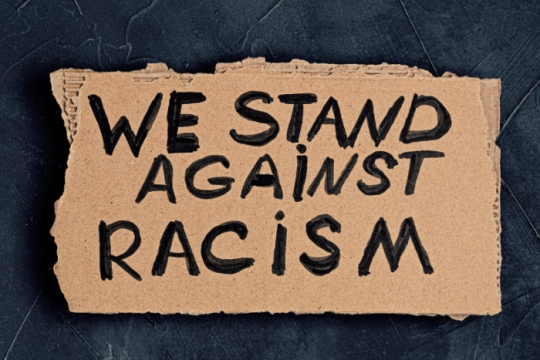Cardboard sign reading WE STAND AGAINST RACISM
