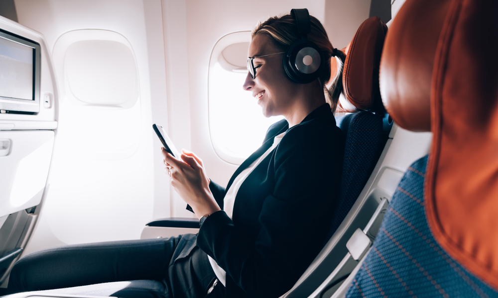 what to pack in your carry-on:Cheerful female passenger in headphones for noise cancellation watching online movie during intercontinental flight in cabin of aircraft
