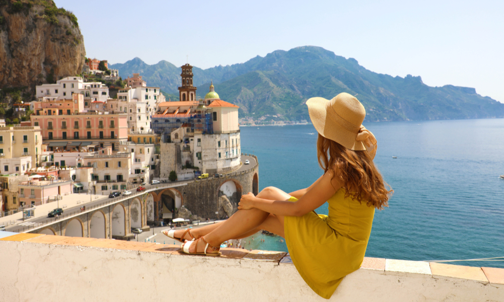The Best Winter Getaways Where You Can Forget the Cold: Beautiful young woman with hat sitting on wall looking at stunning panoramic village of Atrani on Amalfi Coast, Italy