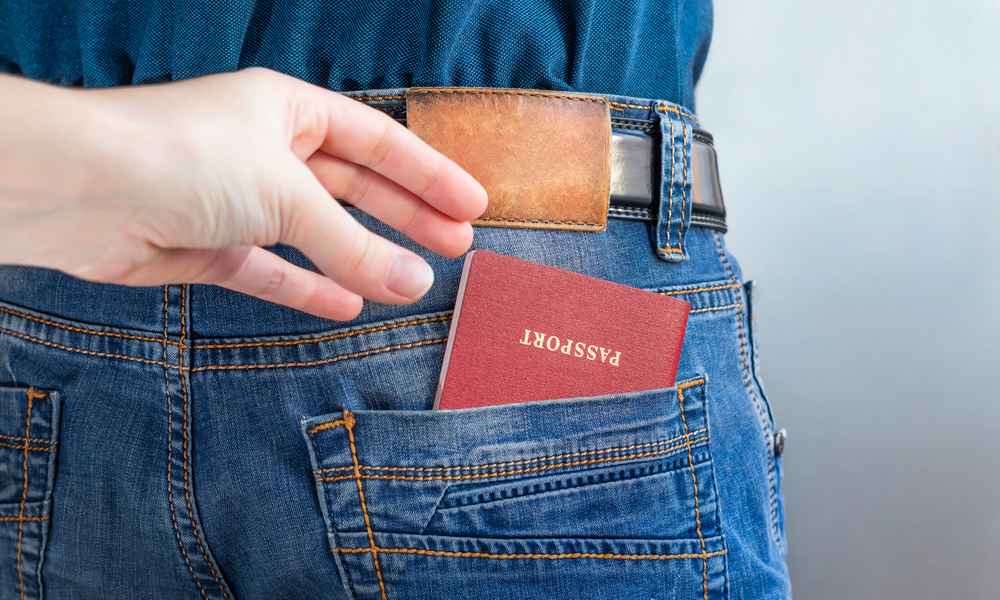 How to Avoid Common Visa Mistakes When Flying Internationally: Hand that stealing document from back jeans pocket.