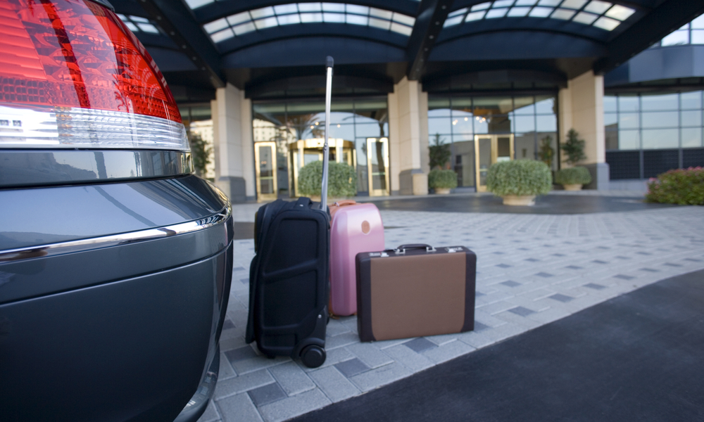 tips for and alternatives to parking at the airport: Luggage beside parked car outside hotel