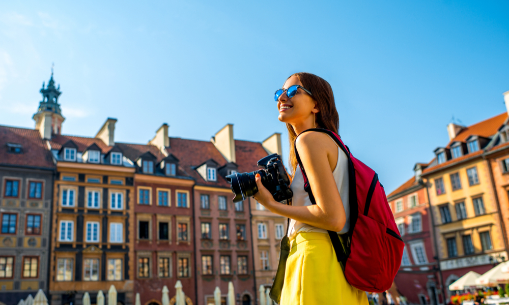How To Plan a Vacation: Female young traveler with backpack and photocamera in the old town market square in Warsaw, Poland