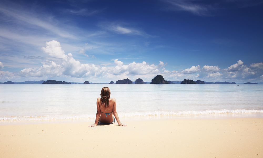 how to travel cheap: woman on a lonely beach during off-season
