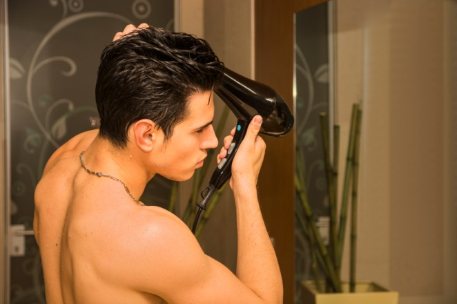 A man blow drying his hair