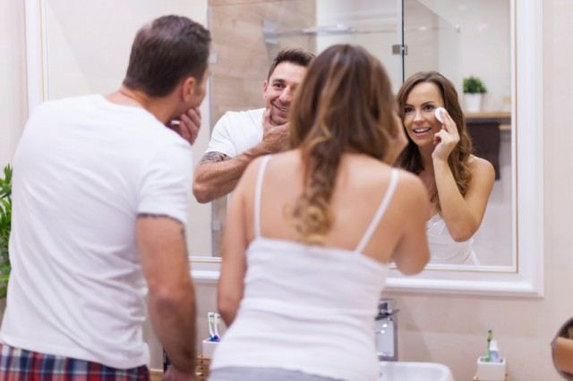 A couple looking in the mirror practicing good skincare