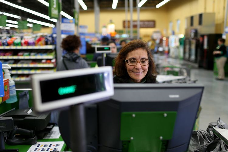 A cashier rings up a customer's purchases at a Walmart