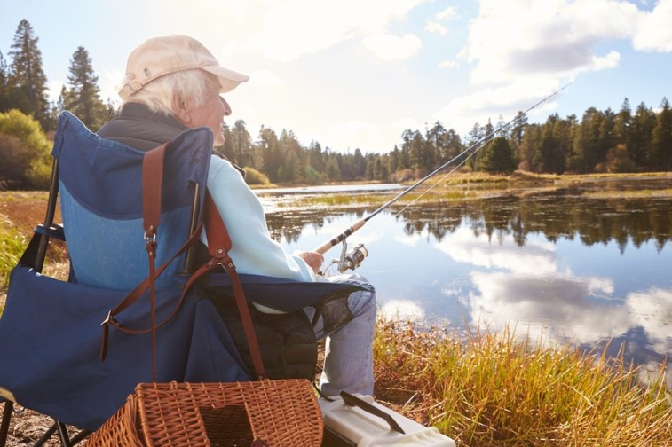 Senior man sits fishing in a lake