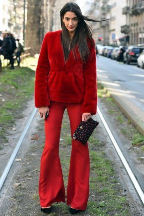 A woman poses in the street before the show for fashion house