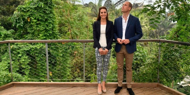 Kate Middleton is wearing a white shirt, dark blazer, and patterned pants while standing next to Prince William