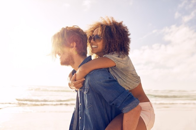 young man carrying his girlfriend on his back at the beach