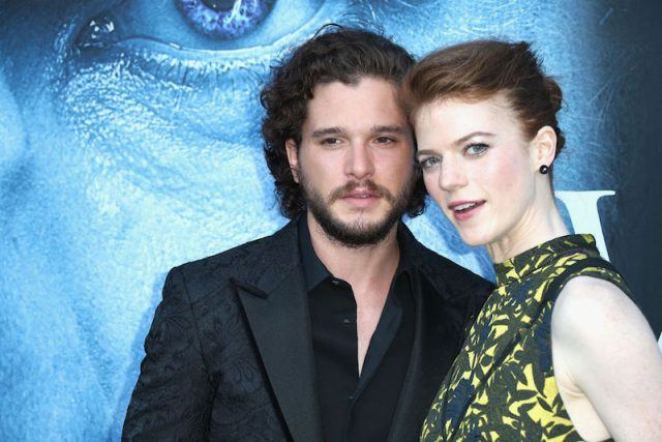 Kit Harington and Rose Leslie pose together behind a wall.
