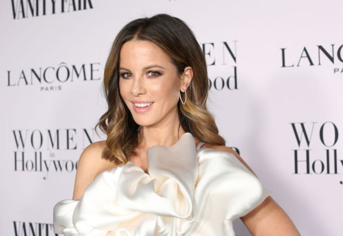 Kate Beckinsale smiling in front of a repetitive background
