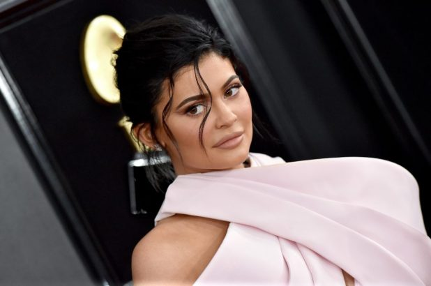 Kylie Jenner is looking at the front of a black background