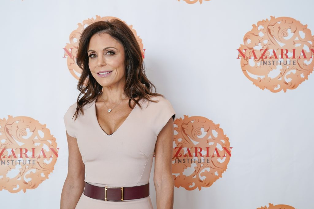 Bethenny Frankel smiles in front of a white background