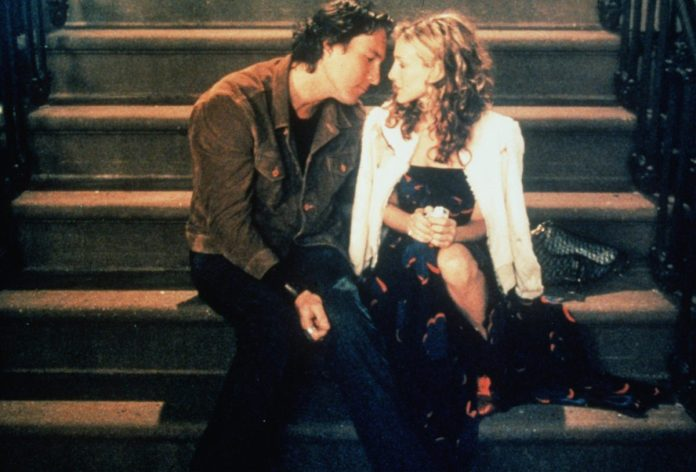 Sarah Jessica Parker as Carrie Bradshaw and John Corbett as Aidan Shaw sit on Carrie's front steps