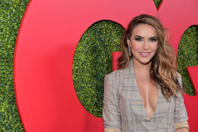 Chrishell Stause smiling in front of a red and green background