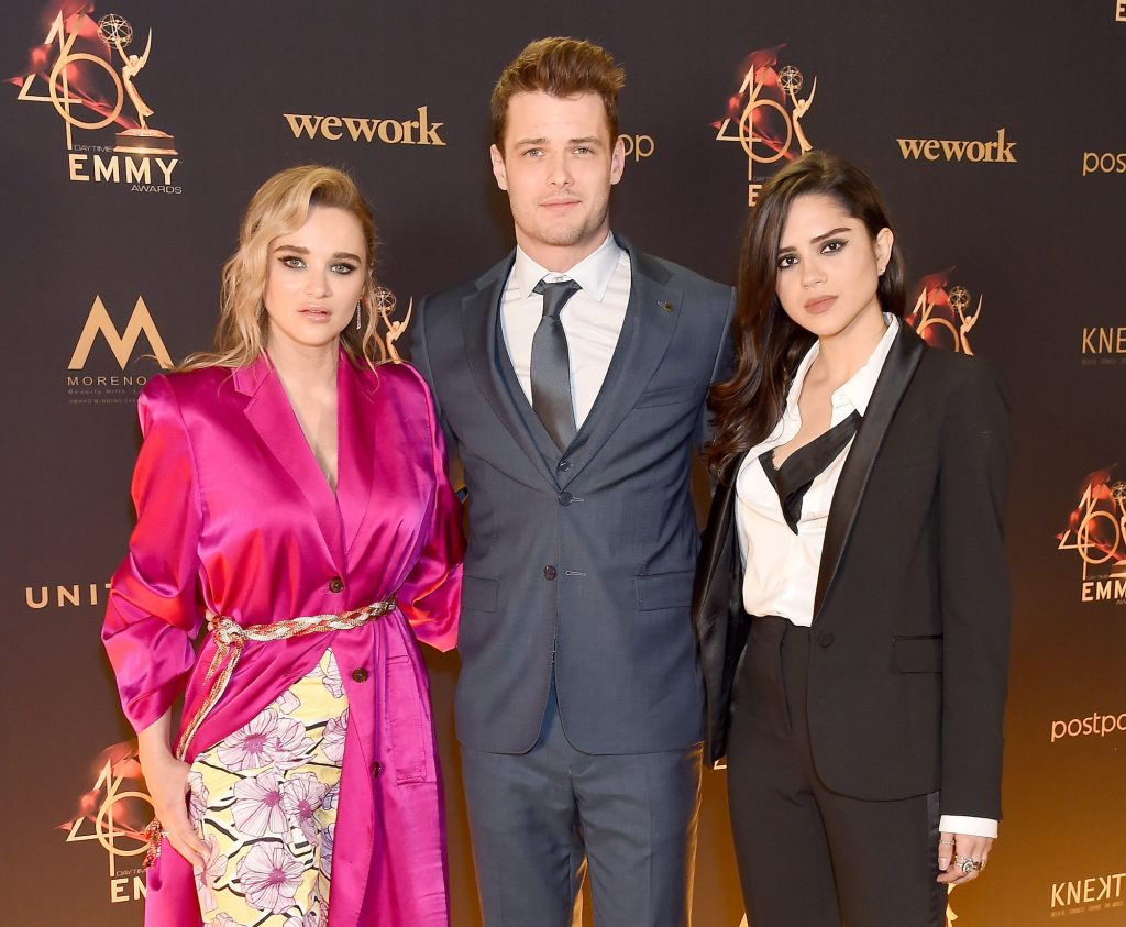 (LR) Actors Hunter King, Michael Mealor, and Sasha Calle in front of a dark background