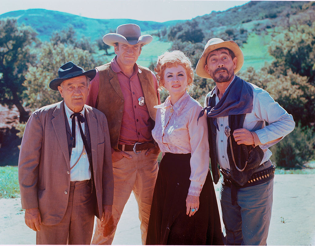 (LR) Milburn Stone as Dr. Galen Adams, James Arness as U.S. Merchant Matt Dillon, Amanda Blake as Kitty Russell, and Ken Curtis as Deputy Marshal Marshal Festus Haggen