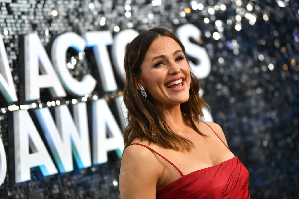 Jennifer Garner smiling in front of a wall with a mirror