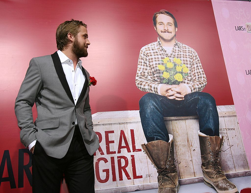Ryan Gosling turned to the side, looking at a picture of his character from 'Lars and the Real Girl'