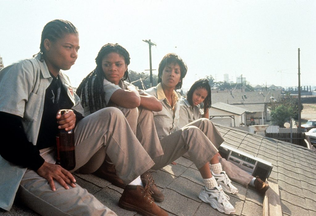 Queen Latifah, Kimberly Elise, Vivica Fox and Jada Pinkett all sitting on the roof of a house in a scene from the 1996 film 'Set It Off'